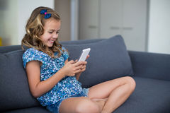 Menina feliz que senta-se no sofá e que usa o telefone celular na sala de visitas Foto de Stock Royalty Free