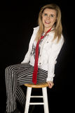Menina feliz que senta-se no tamborete que inclina para trás o sorriso Imagem de Stock