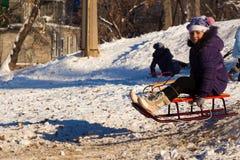 Menina feliz que sledding na neve nevado branca de um monte fotografia de stock royalty free