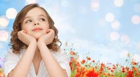 Menina feliz que sonha sobre o fundo do campo da papoila Fotografia de Stock Royalty Free