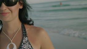 Menina feliz que sorri à câmera que aprecia a praia no alargamento da lente do sol do por do sol filme