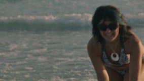 Menina feliz que sorri à câmera que aprecia a praia no alargamento da lente do sol do por do sol video estoque
