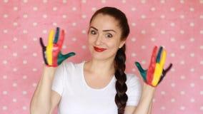 Menina feliz que sorri e que mostra as mãos e as palmas coloridas pintadas Conceito - felicidade, arte, humor criativo, bom, aleg video estoque