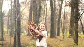 Menina feliz que tem as folhas de jogo do divertimento no ar vídeos de arquivo