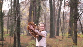Menina feliz que tem as folhas de jogo do divertimento no ar video estoque