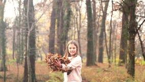 Menina feliz que tem as folhas de jogo do divertimento no ar filme