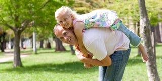 Menina feliz que tem o divertimento com seu pai Imagens de Stock Royalty Free