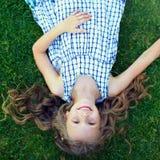 Menina feliz que tem o divertimento encontrar-se na grama Fotografia de Stock