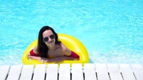 Menina feliz que tem o divertimento na piscina Mulher bonita na associação exterior no hotel de luxo Movimento lento filme