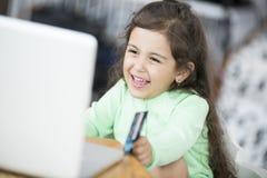 Menina feliz que usa o portátil e o cartão de crédito para comprar em linha em casa Fotografia de Stock Royalty Free
