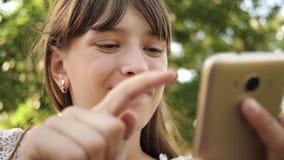Menina feliz que usa o smartphone que lança através das páginas no Internet em um parque em um banco Close-up Milenar novo vídeos de arquivo
