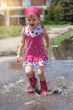 Menina feliz que veste as botas de chuva cor-de-rosa que saltam em uma poça Fotografia de Stock Royalty Free