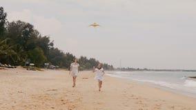 Menina feliz que voa um papagaio, correndo para a câmera com a mãe nova no movimento lento das férias tropicais exóticas da praia filme