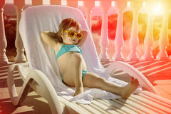 A menina feliz relaxa em um vadio do sol no por do sol Fotos de Stock Royalty Free