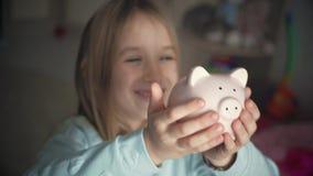 A menina feliz salvar o dinheiro no mealheiro em sua casa Criança que introduz uma moeda em um mealheiro, conceito financeiro int video estoque
