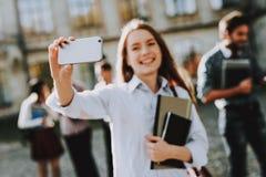 Menina feliz Selfie telefone estudantes pátio fotografia de stock royalty free