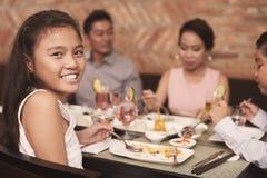 A menina feliz tem o jantar com família foto de stock