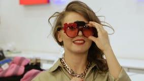A menina feliz tenta sobre óculos de sol engraçados com flores vídeos de arquivo