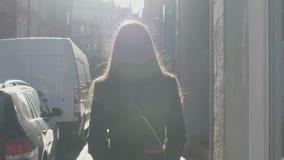 Menina feminino que anda lentamente em feixes mornos da mola do sol para trabalhar, bom humor filme