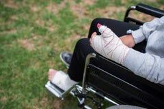 Menina ferida em um detalhe da cadeira de rodas, da m?o e do p? com um emplastro m?dico fotos de stock royalty free