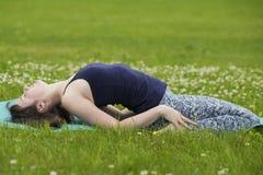 Menina fina que faz a ioga fora no verão na grama verde Imagens de Stock Royalty Free