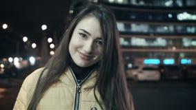 A menina fixa seu cabelo com sua mão, olhando a câmera e sorrindo na cidade da noite video estoque