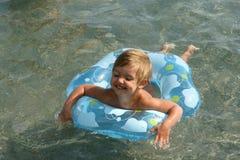 A menina flutua em um anel lifebuoy Foto de Stock