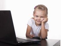 A menina foi confundida do portátil e dos olhares engraçados no quadro Imagem de Stock