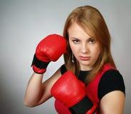 Menina forte bonita em luvas vermelhas para o encaixotamento Foto de Stock Royalty Free