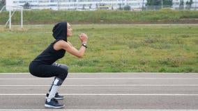 A menina forte faz squatting e saltar no estádio exterior fotografia de stock royalty free
