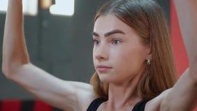 Menina forte que levanta acima de um barbell pesado com esforço video estoque