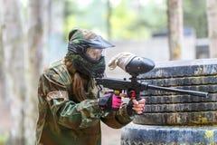 Menina fresca com a arma da pintura que joga o jogo do paintball Imagem de Stock Royalty Free