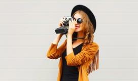 Menina fresca consideravelmente elegante com a câmera retro do filme que veste um chapéu elegante, revestimento marrom foto de stock royalty free