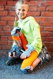 Menina fresca de sorriso feliz do moderno da forma na roupa colorida com os patins de rolo que têm o divertimento fora foto de stock