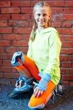 Menina fresca de sorriso feliz do moderno da forma na roupa colorida com os patins de rolo que têm o divertimento fora fotos de stock royalty free