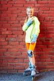 Menina fresca de sorriso feliz do moderno da forma na roupa colorida com os patins de rolo que têm o divertimento fora imagem de stock
