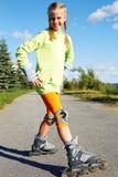 Menina fresca de sorriso feliz do moderno da forma na roupa colorida com patins de rolo foto de stock