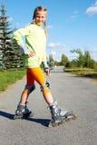 Menina fresca de sorriso feliz do moderno da forma na roupa colorida com patins de rolo fotografia de stock royalty free