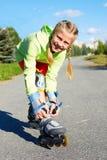 Menina fresca de sorriso feliz do moderno da forma na roupa colorida com patins de rolo imagens de stock royalty free