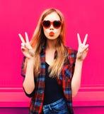 Menina fresca do retrato nos óculos de sol dados forma coração que enviam o beijo doce do ar no rosa colorido foto de stock royalty free