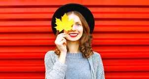 A menina fresca feliz esconde uma folha de bordo amarela do olho em um vermelho fotos de stock