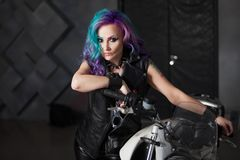 Menina fresca na roupa de couro perto da motocicleta Mulher ? moda nova com cabelo colorido na bicicleta fotografia de stock
