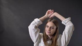 A menina fresca nova é dançar, olhando na câmera, conceito do movimento, fundo cinzento video estoque