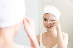 Menina fresca saudável que remove a composição de sua cara com a almofada de algodão fotos de stock