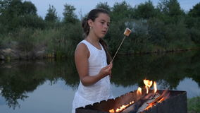 A menina frita marshmallows no fogo perto da lagoa vídeos de arquivo