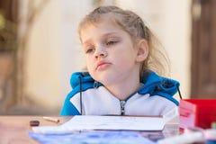 Menina frustrante que senta-se em uma tabela na jarda e em olhares tristes em nenhuma parte Fotografia de Stock Royalty Free