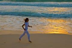 A menina funciona no por do sol ao longo da tira da ressaca Fotografia de Stock Royalty Free