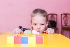 A menina funde a bola de algodão no objetivo Imagens de Stock
