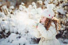 A menina funde a neve com mitenes, em um backg do bokeh dos flocos de neve Fotos de Stock Royalty Free