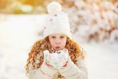 A menina funde a neve com mitenes, em um backg do bokeh dos flocos de neve Foto de Stock Royalty Free